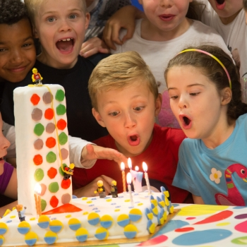Children blowing off the candles on a cake